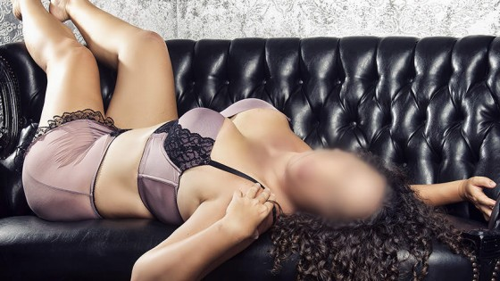 Nashville sensual massage artist lounging in satin lingerie on a leather couch.
