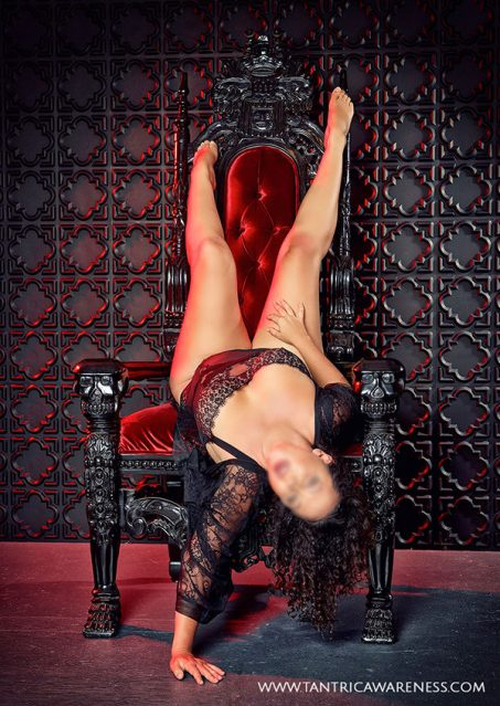 Sensual massage Nashville artist Ava Ananda in sexy black lingerie, lounginging in a red velvet chair.