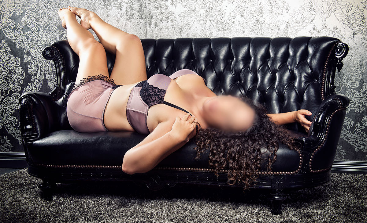 San Diego sensual massage artist lounging in satin lingerie on a leather couch.