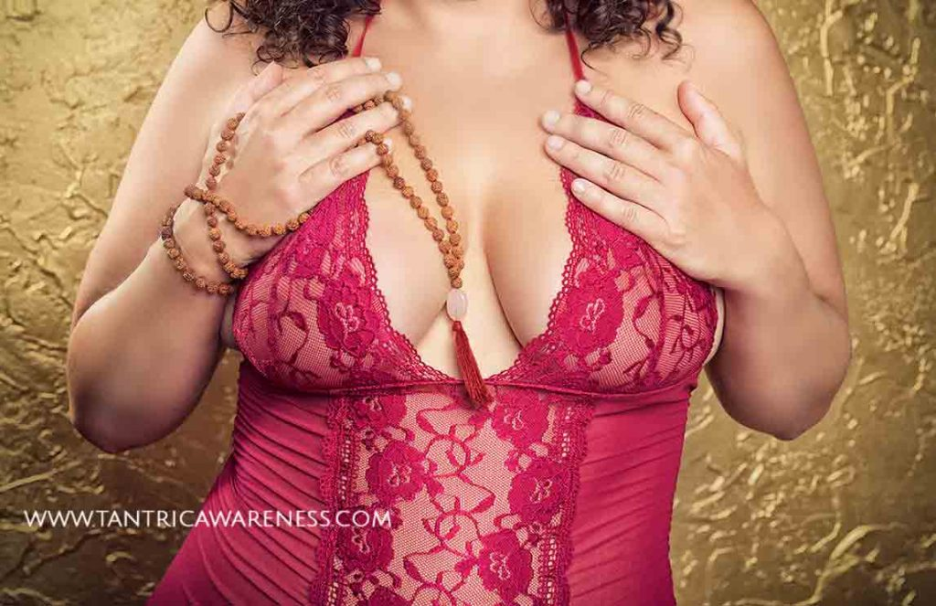 San Diego sensual massage artist Ava Ananda in red, lacy lingerie holding beads.