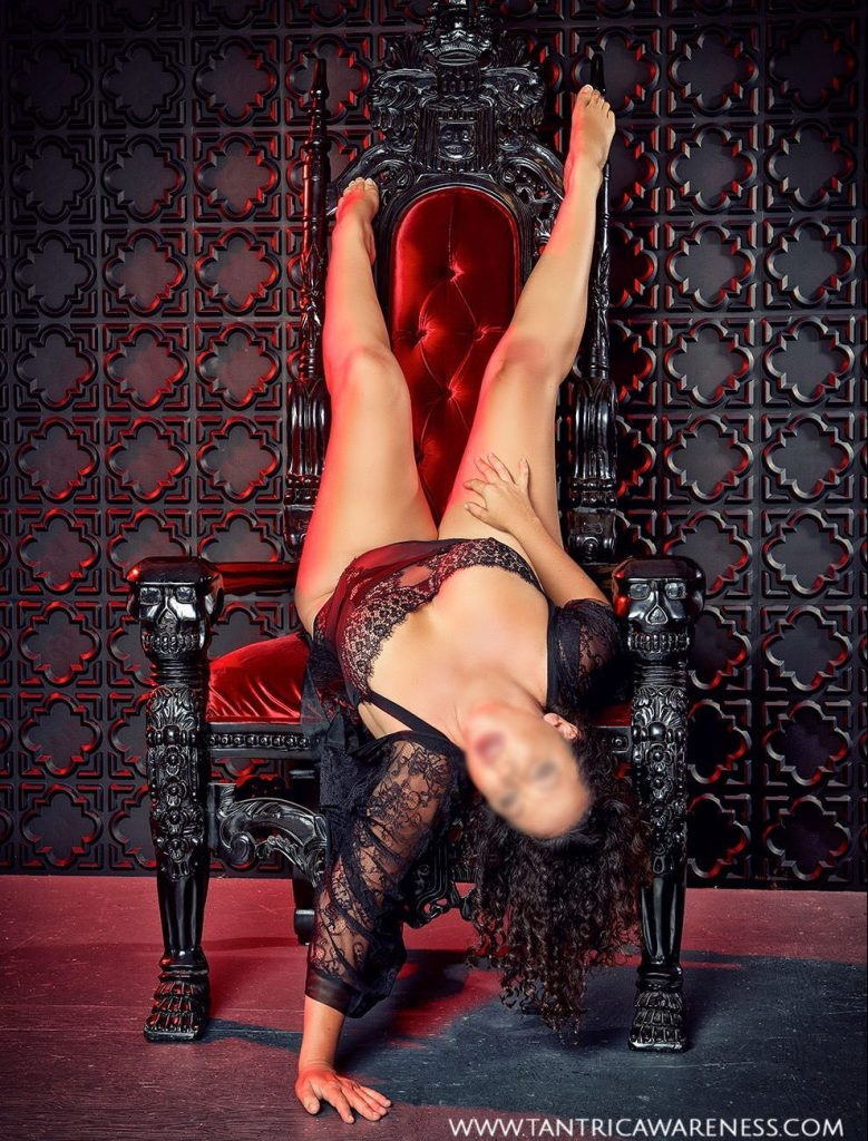 Sensual massage San Diego artist Ava Ananda in sexy black lingerie, lounginging in a red velvet chair.